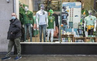 A man wearing a face mask or covering due to the COVID-19 pandemic, stands by Dublin-themed goods in the window display of a souvenir shop in Dublin on October 19, 2020, amid reports that further lockdown restrictions could be imposed to help mitigate the spread of the novel coronavirus. - Ireland will crank up coronavirus restrictions, prime minister Micheal Martin said last week, announcing a raft of new curbs along the border with the British province of Northern Ireland. (Photo by PAUL FAITH / AFP) (Photo by PAUL FAITH/AFP via Getty Images)