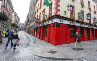 Pedestrians wearing a face mask or covering due to the COVID-19 pandemic, walk past temporarily closed down pubs in Dublin on September 18, 2020, following reports that further lockdown restrictions could be imposed to help mitigate the spread of the novel coronavirus. - Ireland's capital could face further restrictions this weekend after public health experts raised concerns when its 14-day incidence rate jumped to more than 100. (Photo by Paul Faith / AFP) (Photo by PAUL FAITH/AFP via Getty Images)