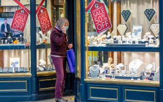 A shopper wearing a face mask or covering due to the COVID-19 pandemic, looks at sale items in the window of a jewellery store in Dublin on October 19, 2020, amid reports that further lockdown restrictions could be imposed to help mitigate the spread of the novel coronavirus. - Ireland will crank up coronavirus restrictions, prime minister Micheal Martin said last week, announcing a raft of new curbs along the border with the British province of Northern Ireland. (Photo by PAUL FAITH / AFP) (Photo by PAUL FAITH/AFP via Getty Images)