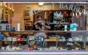A barber wearing PPE of a face mask or covering due to COVID-19, cuts a customer's hair inside a Barbers in Dublin on October 19, 2020, amid reports that further lockdown restrictions could be imposed to help mitigate the spread of the novel coronavirus. - Ireland will crank up coronavirus restrictions, prime minister Micheal Martin said last week, announcing a raft of new curbs along the border with the British province of Northern Ireland. (Photo by PAUL FAITH / AFP) (Photo by PAUL FAITH/AFP via Getty Images)