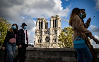 epa08775733 People wearing protective face masks walk near Notre-Dame Cathedral, in Paris, France, 26 October 2020. France is in the midst of a second wave of the COVID-19 coronavirus pandemic, recording a new high of 50,000 daily new cases - although Jean-Francois Delfraissy of France's Scientific Council estimates that bew Covid cases are rising by a rate closer to 100,000 per day. France has currently placed 45 million of its citizen across several 'departments' (counties) under a night-time curfew prohibiting leaving one's house between 9pm and 6am. French President Emmanuel Macron is convening  a defense council on 27 October to draft new measures to battle the rise in Covid-19 cases.  EPA/IAN LANGSDON