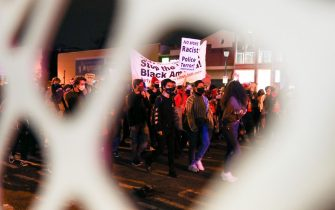 People hold banners and signs during a demonstration in Philadelphia on October 27, 2020, over the police shooting of 27-year-old Black man Walter Wallace. - Hundreds of people demonstrated in Philadelphia late on October 27, with looting and violence breaking out in a second night of unrest after the latest police shooting of a Black man in the US. The fresh unrest came a day after the death of 27-year-old Walter Wallace, whose family said he suffered mental health issues. On Monday night hundreds of demonstrators took to the streets, with riot police pushing them back with shields and batons. (Photo by Gabriella AUDI / AFP) (Photo by GABRIELLA AUDI/AFP via Getty Images)