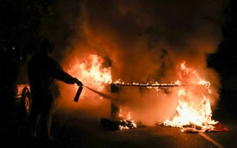 A person uses a fire extinguisher to put out a burning barricade in Philadelphia on October 27, 2020, during a protest over the police shooting of 27-year-old Black man Walter Wallace. - Hundreds of people demonstrated in Philadelphia late on October 27, with looting and violence breaking out in a second night of unrest after the latest police shooting of a Black man in the US. The fresh unrest came a day after the death of 27-year-old Walter Wallace, whose family said he suffered mental health issues. On Monday night hundreds of demonstrators took to the streets, with riot police pushing them back with shields and batons. (Photo by Gabriella AUDI / AFP) (Photo by GABRIELLA AUDI/AFP via Getty Images)