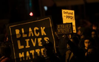 """PHILADELPHIA, PA - OCTOBER 27:  Demonstrators hold placards reading """"BLACK LIVES MATTER,"""" """"Walter Wallace JR."""" and DEFUND PPD"""" as they gather in protest near the location where Walter Wallace, Jr. was killed by two police officers on October 27, 2020 in Philadelphia, Pennsylvania. Protests erupted after the fatal shooting of 27-year-old Wallace Jr, who Philadelphia police officers claimed was armed with a knife. (Photo by Mark Makela/Getty Images)"""