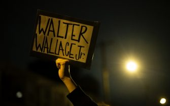 """PHILADELPHIA, PA - OCTOBER 27: A demonstrator holds a placard reading """"WALTER WALLACE JR."""" during a protest near the location where Walter Wallace, Jr. was killed by two police officers on October 27, 2020 in Philadelphia, Pennsylvania. Protests erupted after the fatal shooting of 27-year-old Wallace Jr, who Philadelphia police officers claimed was armed with a knife. (Photo by Mark Makela/Getty Images)"""