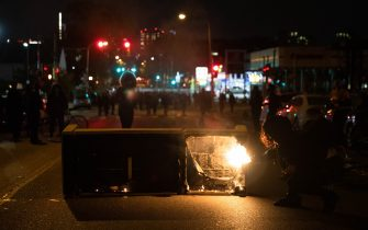 A protester sets a sofa on fire in West Philadelphia on October 27, 2020,  during a demonstration against the fatal shooting of 27-year-old Walter Wallace, a Black man, by police. - Hundreds of people demonstrated in Philadelphia late on October 27, with looting and violence breaking out in a second night of unrest after the latest police shooting of a Black man in the US. The fresh unrest came a day after the death of 27-year-old Walter Wallace, whose family said he suffered mental health issues. On Monday night hundreds of demonstrators took to the streets, with riot police pushing them back with shields and batons. (Photo by GABRIELLA AUDI / AFP) (Photo by GABRIELLA AUDI/AFP via Getty Images)