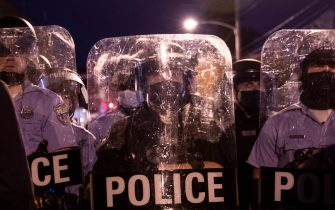 Police in riot gear face protesters marching through West Philadelphia on October 27, 2020, during a demonstration against the fatal shooting of 27-year-old Walter Wallace, a Black man, by police. - Hundreds of people demonstrated in Philadelphia late on October 27, with looting and violence breaking out in a second night of unrest after the latest police shooting of a Black man in the US. The fresh unrest came a day after the death of 27-year-old Walter Wallace, whose family said he suffered mental health issues. On Monday night hundreds of demonstrators took to the streets, with riot police pushing them back with shields and batons. (Photo by GABRIELLA AUDI / AFP) (Photo by GABRIELLA AUDI/AFP via Getty Images)
