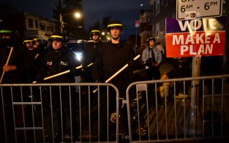 """PHILADELPHIA, PA - OCTOBER 27: Police in tactical gear form a line beside a """"VOTE MAKE A PLAN"""" as demonstrators gather in protest near the location where Walter Wallace, Jr. was killed by two police officers on October 27, 2020 in Philadelphia, Pennsylvania. Protests erupted after the fatal shooting of 27-year-old Wallace Jr, who Philadelphia police officers claimed was armed with a knife. (Photo by Mark Makela/Getty Images)"""