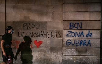 A graffiti saying Enough of evictions, Barcelona War Zone is seen on the wall of Plaza Sant Jaume after the demonstration. Under the slogan Barcelona War Zone, anti-eviction collectives of Barcelona have demonstrated to denounce the wave of evictions suffered by families in Barcelona. After the end of the demonstration there have been some riots and police charges. (Photo by Paco Freire / SOPA Images/Sipa USA)