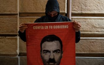 "A man holds a poster depicting Spanish Prime Minister Pedro Sanchez with a Hitlerian moustache that reads ""Trust your government"" during a demonstration against the restrictions imposed to curb rising infections of the novel coronavirus in Granada on October 31, 2020. (Photo by JORGE GUERRERO / AFP) (Photo by JORGE GUERRERO/AFP via Getty Images)"