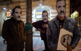 Three people cover their faces with a mask depicting Spanish Prime Minister Pedro Sanchez with a Hitlerian moustache during a demonstration against the restrictions imposed to curb rising infections of the novel coronavirus in Granada on October 31, 2020. (Photo by JORGE GUERRERO / AFP) (Photo by JORGE GUERRERO/AFP via Getty Images)