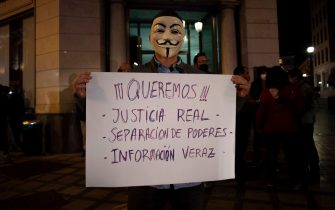 "A man wearing a Guy Fawkes mask holds a sign reading ""We want real justice, separation of power, truthful information"" during a demonstration against the restrictions imposed to curb rising infections of the novel coronavirus in Granada on October 31, 2020. (Photo by JORGE GUERRERO / AFP) (Photo by JORGE GUERRERO/AFP via Getty Images)"