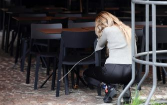 epa08788043 An employee of a bar unlocks the chairs at a shopping street in Frankfurt am Main, Germany, 31 October 2020. The State of Hesse's authorities imposed tightened coronavirus restrictions, including wearing a mask in downtown, as the number of coronavirus cases all over in the country has exceeded the level of 50 new infections per 100,000 residents.  EPA/RONALD WITTEK