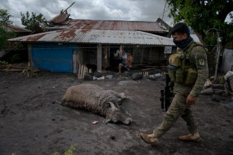 GUINOBATAN, PHILIPPINES - NOVEMBER 2: (EDITORS NOTE: Image depicts death.) A dead carabao lies on a road as a police officer walks by in the destroyed village of San Francisco in the aftermath of Super Typhoon Goni on November 2, 2020 in Guinobatan, Philippines. Super Typhoon Goni, this year's most powerful storm in the world, hit the Philippines with wind gusts of up to 165 miles per hour on November 1. The typhoon left at least ten people killed. (Photo by Jes Aznar/Getty Images)