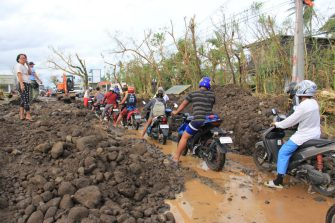Motorists make their way through boulders washed from nearby Mayon volcano along a damaged road  after super Typhoon Goni hit the town of Malilipot, Albay province, south of Manila on November 1, 2020. - At least seven people were killed as Typhoon Goni pounded the Philippines on November 1, ripping off roofs, toppling power lines and causing flooding in the hardest-hit areas where hundreds of thousands have fled their homes. (Photo by Charism SAYAT / AFP) (Photo by CHARISM SAYAT/AFP via Getty Images)