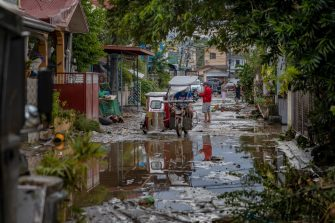BATANGAS, PHILIPPINES - NOVEMBER 02: A tricycle travels along a road filled with mud left behind by flashfloods caused by Typhoon Goni on November 2, 2020 in Batangas city, south of Manila, Philippines. Super Typhoon Goni, this year's most powerful storm in the world, hit the Philippines with wind gusts of up to 165 miles per hour on November 1. The typhoon left at least ten people killed. (Photo by Ezra Acayan/Getty Images)