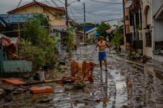 BATANGAS, PHILIPPINES - NOVEMBER 02: A man walks along a road filled with mud left behind by flashfloods caused by Typhoon Goni on November 2, 2020 in Batangas city, south of Manila, Philippines. Super Typhoon Goni, this year's most powerful storm in the world, hit the Philippines with wind gusts of up to 165 miles per hour on November 1. The typhoon left at least ten people killed. (Photo by Ezra Acayan/Getty Images)