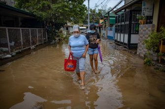 BATANGAS, PHILIPPINES - NOVEMBER 02: Residents wade through muddy floodwater caused by Typhoon Goni on November 2, 2020 in Batangas city, south of Manila, Philippines. Super Typhoon Goni, this year's most powerful storm in the world, hit the Philippines with wind gusts of up to 165 miles per hour on November 1. The typhoon left at least ten people killed. (Photo by Ezra Acayan/Getty Images)