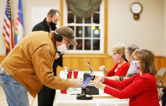 epa08795054 Gary Kuntz (L) of Edinburg, Ohio, the first voter in line at the Edinburg Town Hall polling location receives his ballot from Poll worker Debbie Stanatis (R) at a polling location at the Edinburg Town Hall in Edinburg, Ohio, USA, 03 November 2020. Americans vote on Election Day to choose between re-electing Donald J. Trump or electing Joe Biden as the 46th President of the United States to serve from 2021 through 2024.  EPA/DAVID MAXWELL