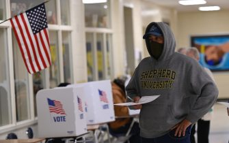 """A voters casts his ballot at a polling station on US Election Day in Winchester, Virginia early November 3, 2020. - Polling stations opened in New York, New Jersey and Virginia early November 3, marking the start of US Election Day as President Donald Trump seeks to beat forecasts and defeat challenger Joe Biden. The vote is widely seen as a referendum on Trump and his uniquely brash, bruising presidency that Biden urged Americans to end to restore """"our democracy."""" (Photo by ANDREW CABALLERO-REYNOLDS / AFP) (Photo by ANDREW CABALLERO-REYNOLDS/AFP via Getty Images)"""