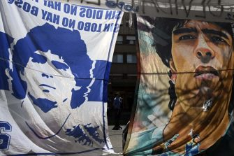 Flags depicting Argentine former football star and coach of Gimnasia y Esgrima La Plata Diego Maradona, hang outside the Ipensa clinic where Maradona has been admitted, in La Plata, Buenos Aires province, on November 3, 2020. - Argentine football great Diego Maradona was admitted to hospital Monday for medical checks, his personal doctor announced. (Photo by JUAN MABROMATA / AFP) (Photo by JUAN MABROMATA/AFP via Getty Images)