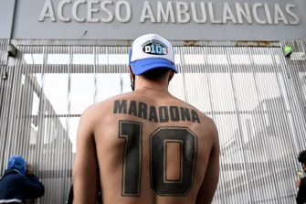 A supporter of Argentine former football star and coach of Gimnasia y Esgrima La Plata Diego Maradona displays his tattoo, outside the hospital where he will undergo brain surgery for a blood clot, in Olivos, Buenos Aires province, on November 3, 2020. (Photo by JUAN MABROMATA / AFP) (Photo by JUAN MABROMATA/AFP via Getty Images)