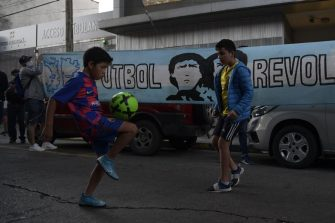 Kids play football near the entrance of the Hospital where Argentine former football star and coach of Gimnasia y Esgrima La Plata Diego Maradona, will undergo brain surgery for a blood clot, in Olivos, Buenos Aires province, on November 3, 2020. (Photo by JUAN MABROMATA / AFP) (Photo by JUAN MABROMATA/AFP via Getty Images)