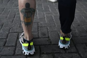 A supporter of Argentine former football star and coach of Gimnasia y Esgrima La Plata Diego Maradona shows his tattoo, outside the hospital where he will undergo brain surgery for a blood clot, in Olivos, Buenos Aires province, on November 3, 2020. (Photo by JUAN MABROMATA / AFP) (Photo by JUAN MABROMATA/AFP via Getty Images)