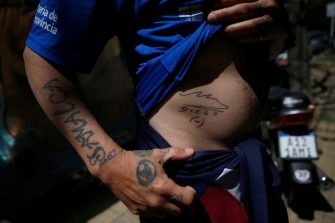 LA PLATA, ARGENTINA - NOVEMBER 03: A man shows his tattoo of Diego Maradona's signature outside Sanatorio Ipensa where the former footballer and current coach of Gimnasia Esgrima La Plata remains hospitalized on November 03, 2020 in La Plata, Argentina. Maradona arrived to the clinic on Monday night with signs of depression, three days after turning 60 years old. (Photo by Stringer/Getty Images)