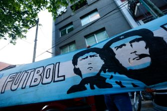 OLIVOS, ARGENTINA - NOVEMBER 03: An Argentina flag depicting Diego Maradona and Ernesto Che Guevara hangs outside of Clínica Olivos on November 03, 2020 in Olivos, Argentina. Personal doctor of Maradona, Leopoldo Luque, confirmed the former footballer will under a surgery to treat a clot in his brain. Maradona, who turned 60 on Friday 30, had spent the night of Monday hospitalized after being admitted with symptoms of depression. (Photo by Marcos Brindicci/Getty Images)