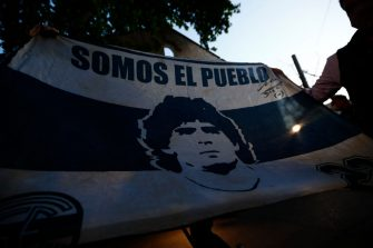 OLIVOS, ARGENTINA - NOVEMBER 03: Fans show a flag of Gimnasia Esgrima La Plata with the face of Diego Maradona at Clínica Olivos on November 03, 2020 in Olivos, Argentina. Personal doctor of Maradona, Leopoldo Luque, confirmed the former footballer will under a surgery to treat a clot in his brain. Maradona, who turned 60 on Friday 30, had spent the night of Monday hospitalized after being admitted with symptoms of depression. (Photo by Marcos Brindicci/Getty Images)