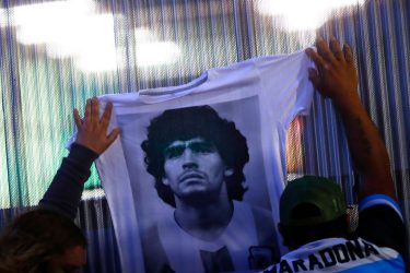OLIVOS, ARGENTINA - NOVEMBER 03: Fans hold a jersey with the face of Diego Maradona at Clínica Olivos on November 03, 2020 in Olivos, Argentina. Personal doctor of Maradona, Leopoldo Luque, confirmed the former footballer will under a surgery to treat a clot in his brain. Maradona, who turned 60 on Friday 30, had spent the night of Monday hospitalized after being admitted with symptoms of depression. (Photo by Marcos Brindicci/Getty Images)