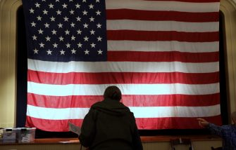 epa08795145 A voter pauses in front of the US national flag before casting a ballot at a polling location at the Old Stone School in Hillsboro, Virginia, USA, 03 November 2020. Americans vote on Election Day to choose between re-electing Donald J. Trump or electing Joe Biden as the 46th President of the United States to serve from 2021 through 2024.  EPA/MICHAEL REYNOLDS
