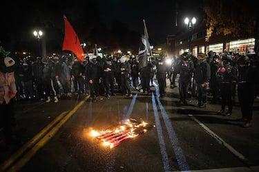 epa08799708 Antifascist protesters watch a flag burn in Portland, Oregon, USA, 04 November 2020. Portland Police declared a riot after protesters began damaging businesses.  EPA/CHRISTIAN MONTERROSA