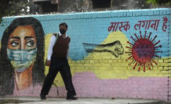 epa08804147 An Indian man passes by a mural on a wall to spread awareness about wearing a protective face mask to avoid spread of  novel coronavirus in New Delhi, India, 07 November 2020. According to reports, India became the second worst-hit country by the spread of novel coronavirus which causes Covid-19 disease, as Indian tally rose to over 8.3 million cases, only behind the United States.  EPA/RAJAT GUPTA