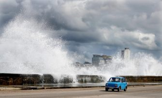 epaselect epa08810300 A vehicle transits the Malecon as waves crashes and gray clouds hang over the Cuban capital caused by tropical storm Eta, in Havana, Cuba, 09 November 2020.  EPA/Yander Zamora