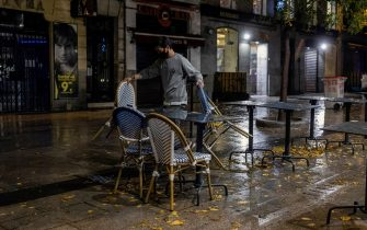 epa08774308 A bartender takes chairs and tables inside a bar in downtown Madrid, Spain, before a curfew was imposed late 25 October 2020.  A curfew from midnight to 06:00 am was imposed from last night in Madrid, after central Government's declared a new state of emergency in the country. Madrid's regional authorities have imposed mobility restrictions in 32 areas, as well, to try to avoid the spreading of COVID-19 virus disease.  EPA/Rodrigo Jimenez
