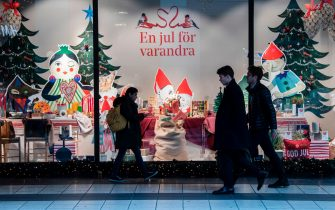 People pass a Christmas decorated shopping window in central Stockholm on November 10, 2020, amid the novel coronavirus COVID-19 pandemic. (Photo by Fredrik SANDBERG / TT News Agency / AFP) / Sweden OUT (Photo by FREDRIK SANDBERG/TT News Agency/AFP via Getty Images)