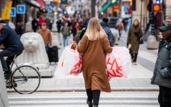 A woman carries plastic bags at the Drottninggatan shopping street in central Stockholm on November 10, 2020, amid the novel coronavirus COVID-19 pandemic. (Photo by Fredrik SANDBERG / TT News Agency / AFP) / Sweden OUT (Photo by FREDRIK SANDBERG/TT News Agency/AFP via Getty Images)