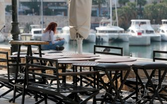 epa08798438 A girl sits outside a closed cafe at the Piraeus port, Greece, 04 November 2020. Greek government has decided that all cafes and restaurants will be closed in all high risk regions all over the country in order to stem the spread of the coronavirus (Covid-19) disease. Greece has been experiencing a rising rate of coronavirus infections, authorities said, with 26 regions in 'red alert', particularly in Thessaloniki and Serres, which were placed under full lockdown for the next two weeks.  EPA/PANTELIS SAITAS