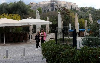 epa08798453 People wearing protective masks pass by closed restaurant in the area of Thiseio under the Acropolis Hill in central Athens, Greece, 04 November 2020. Greek government has decided that all cafes and restaurants will be closed in all high risk regions all over the country in order to stem the spread of the coronavirus (Covid-19) disease. Greece has been experiencing a rising rate of coronavirus infections, authorities said, with 26 regions in 'red alert', particularly in Thessaloniki and Serres, which were placed under full lockdown for the next two weeks.  EPA/PANTELIS SAITAS