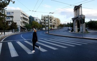 epa08803980 A pedestrian wears a protective mask as she crosses the deserted Amalias Avenue in front of the ancient Adrian's gate, on the first day of the lockdown, in Athens, Greece, 07 November 2020. Greek Prime Minister Kyriakos Mitsotakis announced a ban on public movement as of 06:00 on 07 November introducing the strictest measure, to stem the spread of the coronavirus pandemic in Greece.  EPA/ORESTIS PANAGIOTOU