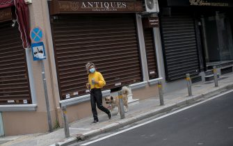epa08816017 A pedestrian wearing a face mask walks her dog in front of a closed antique shop at the commercial district of Kolonaki during the second lockdown of the country, to stem the spread of the coronavirus pandemic, in central Athens, Greece, 12 November 2020. New restrictions have been enforced in Greece amid a second wave of COVID-19 infections sweeping through Europe. An overnight curfew will come into effect across the country on 13 November.  During the hours of 21:00 to 05:00 every day, citizens must restrict their outings to the bare minimum: only for work, health emergencies and walking their pets.  EPA/KOSTAS TSIRONIS