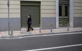 epa08816018 A pedestrian wearing a face mask walks her dog in front of a closed shop at the commercial district of Kolonaki during the second lockdown of the country, to stem the spread of the coronavirus pandemic, in central Athens, Greece, 12 November 2020. New restrictions have been enforced in Greece amid a second wave of COVID-19 infections sweeping through Europe. An overnight curfew will come into effect across the country on 13 November.  During the hours of 21:00 to 05:00 every day, citizens must restrict their outings to the bare minimum: only for work, health emergencies and walking their pets.  EPA/KOSTAS TSIRONIS