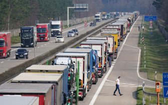 FURSTENWALDE, GERMANY - MARCH 17: A truck driver walks next to his truck among a line of trucks stretching over 40km on the A12 highway towards Germany's border to Poland on March 17, 2020 near Furstenwalde, Germany. The Polish government recently imposed heavy restrictions on its border to Germany in an effort to stem the spread of the coronavirus and had promised cargo would still be allowed to cross. (Photo by Sean Gallup/Getty Images)