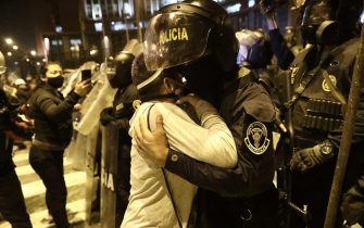 epa08821090 A woman hugs a policeman during a protest against the new government of President Manuel Merino, in San Martin de Lima square, in Lima, Peru, 14 November 2020. Merino took office on 10 November amid a controversial constitutional process after the dismissal of former President Martin Vizcarra for 'moral incapacity' by Peruvian Congress.  EPA/Aldair Mejia