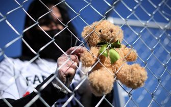 WASHINGTON, DC - NOVEMBER 16: A volunteer with pro-immigration group Families Belong Together, attaches one of 600 teddy bears to a chainlink cage which 'representing the children still separated as a result of U.S. immigration policies' on the National Mall November 16, 2020 in Washington, DC. Organized by the National Domestic Workers Alliance, Families Belong Together was formed in 2018 in response to the Trump Administration's policy of separating children from their parents after they enter the U.S. to seek refuge, resulting in hundreds of children unable to be reunited with their families because of poor administration and tracking. (Photo by Chip Somodevilla/Getty Images)