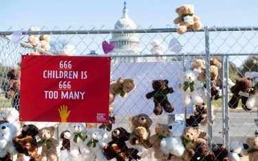 TOPSHOT - Volunteers and staff with Families Belong Together and the Franciscan Action Network (FAN), install more than 600 teddy bears in a chain-link cage to represent children separated from their families by US immigration policies, during a protest exhibit near the US Capitol in Washington, DC, November 16, 2020. (Photo by SAUL LOEB / AFP) (Photo by SAUL LOEB/AFP via Getty Images)