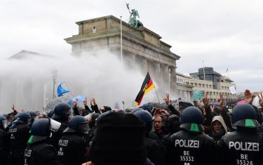 epa08827154 Riot police uses  water cannons to break up a demonstration against German coronavirus restrictions, near the Brandenburg Gate in Berlin, Germany, 18 November 2020. While German interior minister prohibited demonstrations around the Reichstag building during the parliamentary Bundestag session people gathered to protest against government-imposed semi-lockdown measures aimed at curbing the spread of the coronavirus pandemic. Since 02 November, all restaurants, bars, cultural venues, fitness studious, cinemas and sports halls are forced to close for four weeks as a lockdown measure to rein in skyrocketing coronavirus infection rates.  EPA/FILIP SINGER