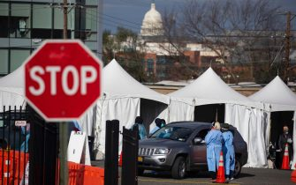 epa08827545 People in vehicles are tested with a swab at a drive-thru COVID-19 testing site operated by the District of Columbia, with the US Capitol seen in the background, in Washington, DC, USA, 18 November 2020. The coronavirus COVID-19 pandemic shows no signs of slowing down in the United States, where record daily cases and hospitalizations are straining the health care system.  EPA/MICHAEL REYNOLDS